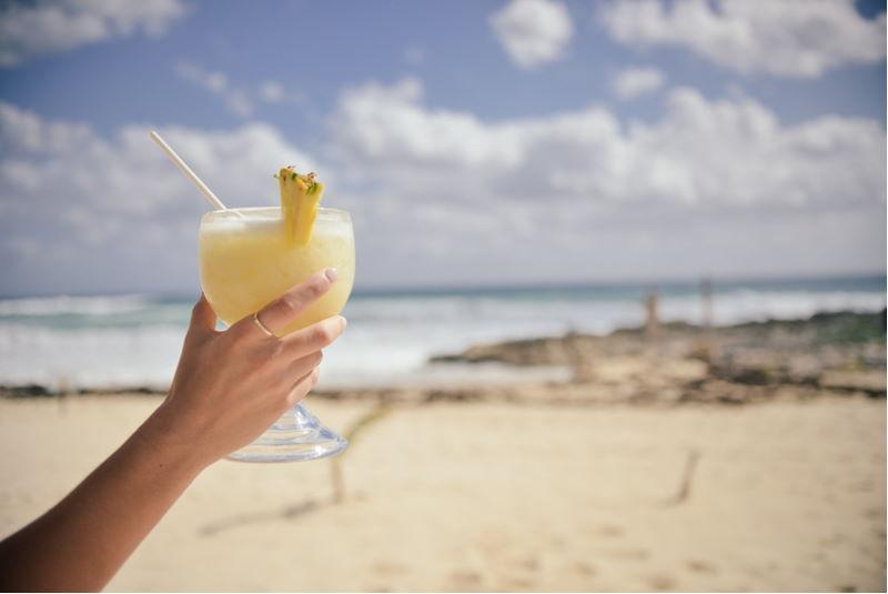 Frau mit Cocktail im Urlaub am Strand.