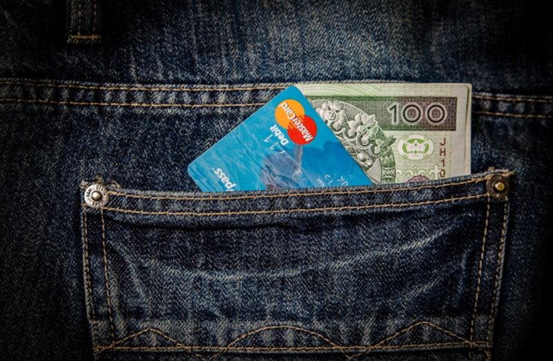 MasterCard und Geldschein ragen aus einer Gesäßtasche einer Jeans heraus